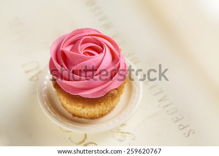 cupcake with a pink rose decoration - stock photo