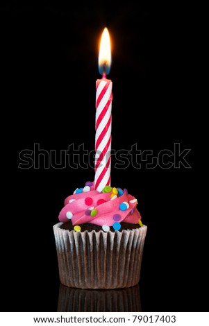 cupcake with burning candle over black background - stock photo