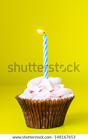 Cupcake with candle on color background - stock photo
