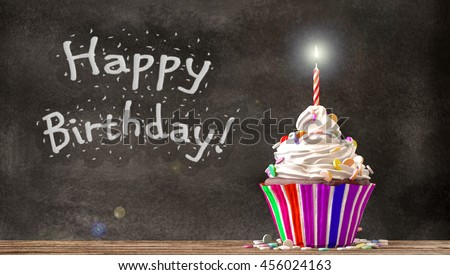 Cupcake with cream, candies and a candle on a wooden table with Happy Birthday written on a blackboard background. Empty free copy space available. 3D Rendering - stock photo