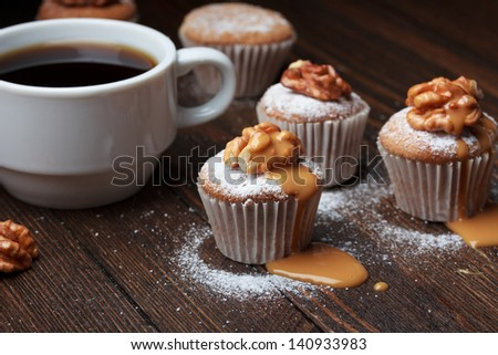 Cupcake with nuts and caramel on old wooden table - stock photo