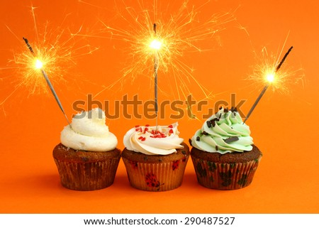 cupcake with sparkler against a orange background. birthday - stock photo