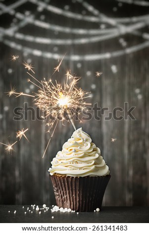 Cupcake with sparkler against a wooden background - stock photo