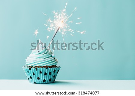 Cupcake with sparkler against blue - stock photo