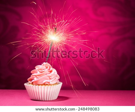 Cupcake with sprinkles and  a sparkler over a pink background. - stock photo