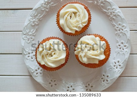Cupcake with vanilla cream on white plate and white wooden background - stock photo