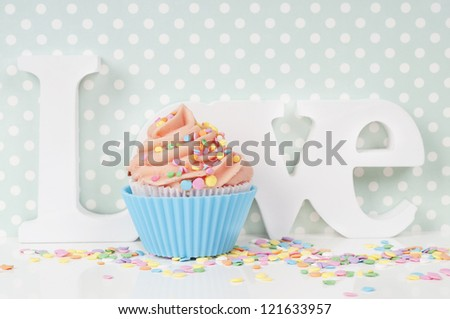 cupcake with whipped cream in a blue love setting - stock photo