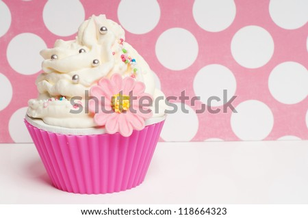 cupcake with whipped cream on pink dotted background - stock photo