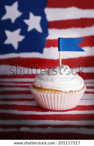 Cupcake with white Topping and Blue Flag with Copyspace for Your Text in front of an American Flag like Background - stock photo