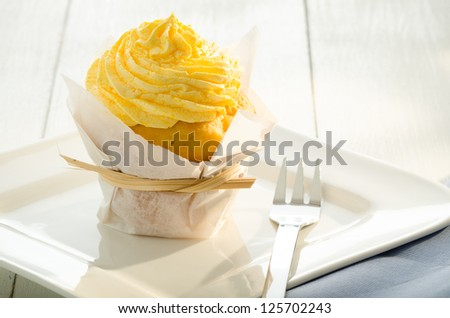 cupcake with yellow cream and fresh mint leaves as decoration on white plate - stock photo