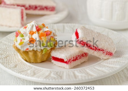 Cupcakes and coconut raspberry dessert on a plate, a cup on a white background. Selective focus - stock photo
