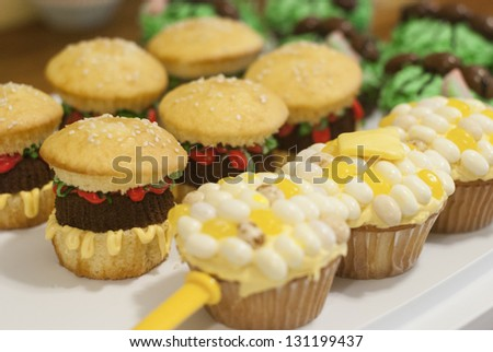 Cupcakes decorated to look like hamburgers and corn on the cob - stock photo