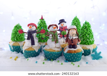 Cupcakes decorated with a sugar kid in a fur hat snowmen and trees on the Christmas lights background. - stock photo
