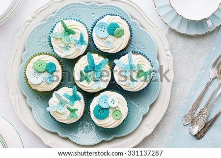 Cupcakes decorated with sugarpaste butterflies and buttons - stock photo