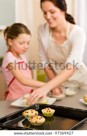 Cupcakes little girl decorate with sprinkles muffins with mother - stock photo