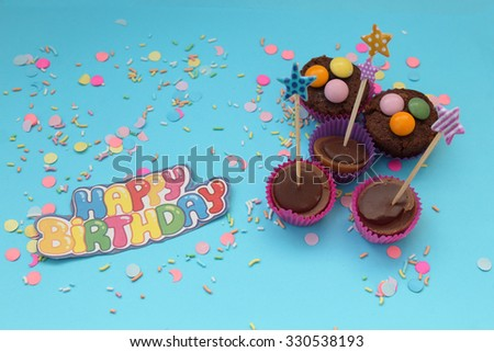 Cupcakes on blue confetti background - happy birthday card - stock photo