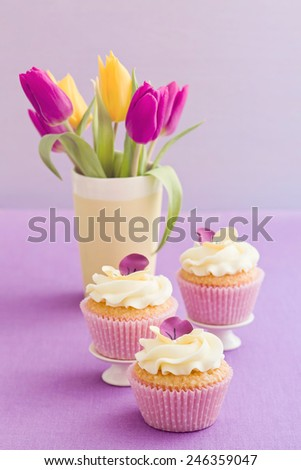 Cupcakes with buttercream and pansy sugar flowers - stock photo