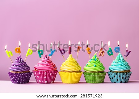 "Cupcakes with candles spelling the words ""happy birthday"" - stock photo"