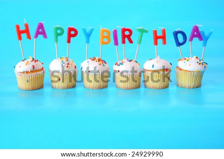 Cupcakes with Happy Birthday Candles on them against a blue background and plenty of room for copy space. - stock photo