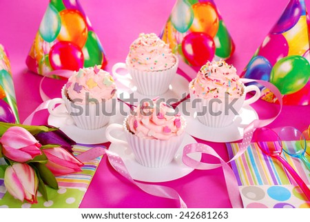 cupcakes with pink cream and sugar sprinkles in white tea cup shape molds for birthday party - stock photo