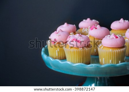 Cupcakes with pink frosting against dark gray background, selective focus - stock photo