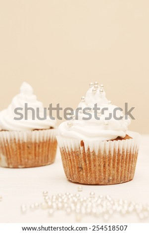 Cupcakes with whipped cream,  White cupcakes with decorative silver sprinkles. Shallow dof.  - stock photo