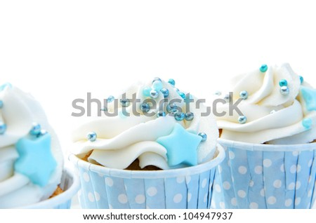 Cupcakes with white frosting, blue decorations and polka dot wrappers - stock photo