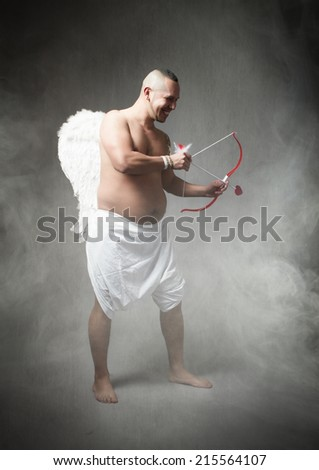 Cupid ready to hit with feather - stock photo