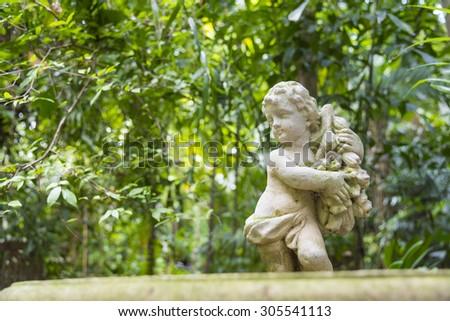 Cupid sculpture in the garden - stock photo