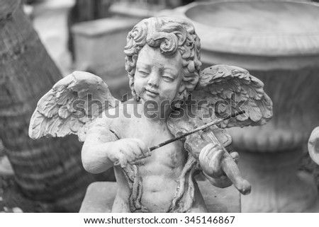 cupid statue, black and white - stock photo
