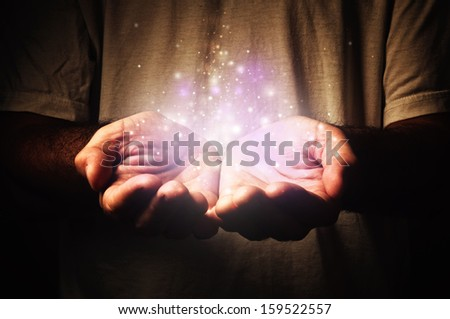 Cupped hands holding magic particles. Open hands of a man. Holding, giving, reaching, taking concept. - stock photo