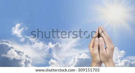 Cupped Hands in Prayer Position -  Male hands cupped together in prayer position on a wide sunny blue sky background with beautiful cloud formations and plenty of copy space on the left   side  - stock photo