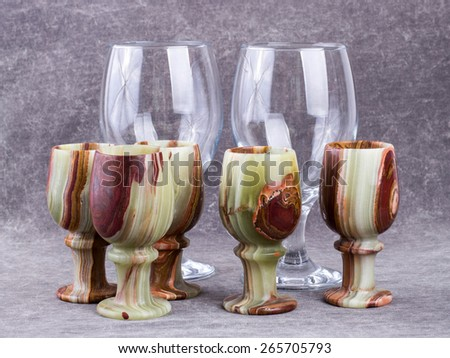 Cups made of natural stone and wine glasses. - stock photo