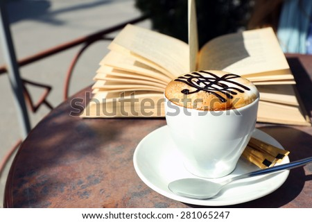Cups of cappuccino with treble clef on foam  and book on table in cafe - stock photo