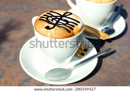 Cups of cappuccino with treble clef on foam on table in cafe - stock photo