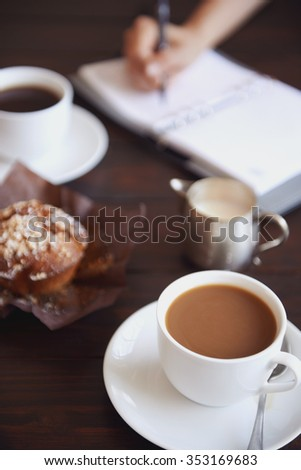 Cups of coffee with a muffin and a  person writing in her daily planner in the background - stock photo