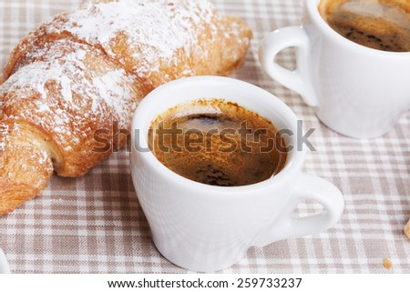 Cups of coffee with croissant on fabric background - stock photo