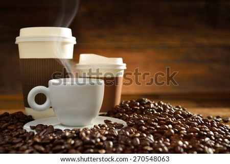 Cups of coffee with smoke and coffee beans on old wooden background - stock photo