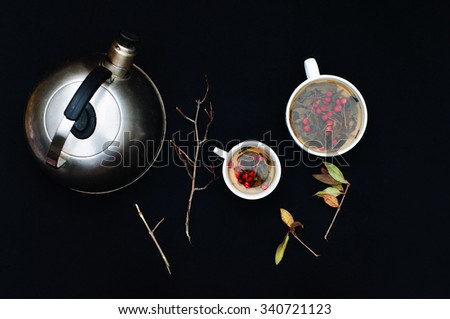 Cups of fresh herbal tea on black table. Cup of green herbal tea. Herbal tea. Botanical. Branch. Top view. Black  background. White tea cups. Kettle. - stock photo