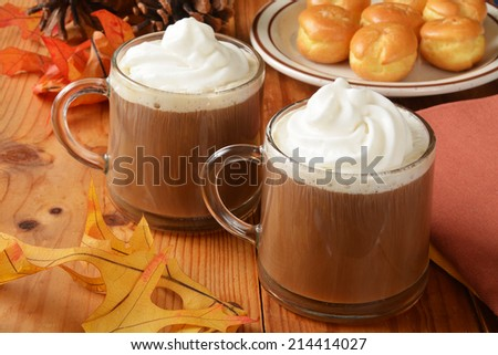Cups of hot chocolate with whipped cream and cream puffs on a holiday table - stock photo