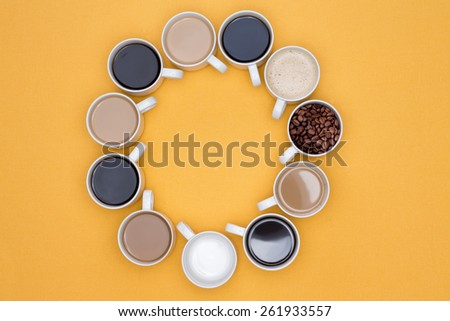Cups of Hot Coffee in Different Flavors Arranged in Circle on a Yellow Background, Captured in High Angle View. - stock photo