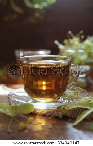 Cups of linden tea with linden flowers on wooden background in sunshine light - stock photo