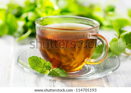 cups of tea with mint on wooden table - stock photo