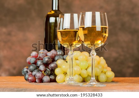 cups of white wine in front of grape and bottle - stock photo