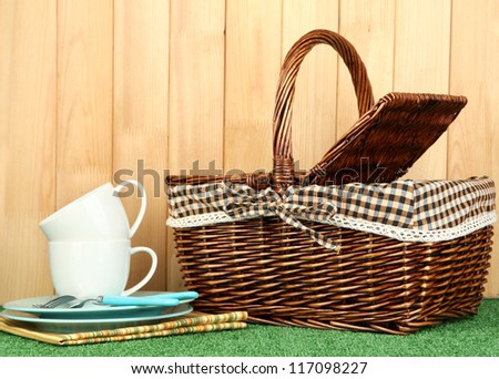 cups, plates and basket on grass on wooden background - stock photo