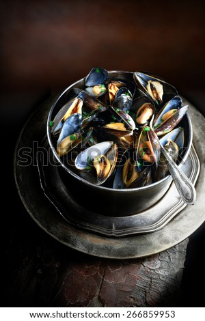 Curated aerial image of perfectly steamed cooked garlic mussels in a antique Victorian cooking pot against a dark, rustic background with copy space. Concept image for a restaurant menu cover design. - stock photo