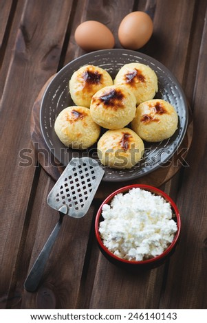 Curd pancakes with ingredients over rustic wooden background, studio shot - stock photo