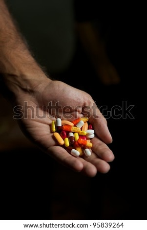 Cure, a hand with mixed pills - stock photo