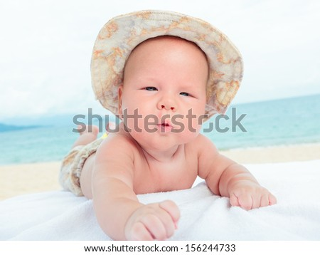 Cure baby laying on the sunbed at the beach - stock photo