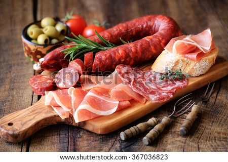 Cured meat platter of traditional Spanish tapas - chorizo, salsichon, jamon serrano, lomo - erved on wooden board with olives and bread - stock photo
